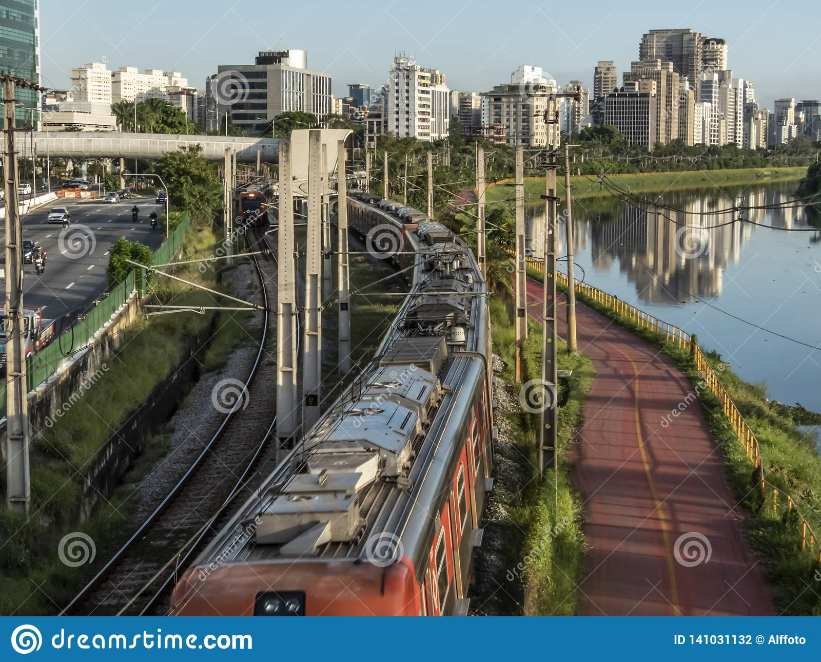 Ansicht von Gebäuden, VON CPTM-Zug, von Verkehr von Fahrzeugen und von Fluss in der begrenzten Pinheiros-Fluss-Allee