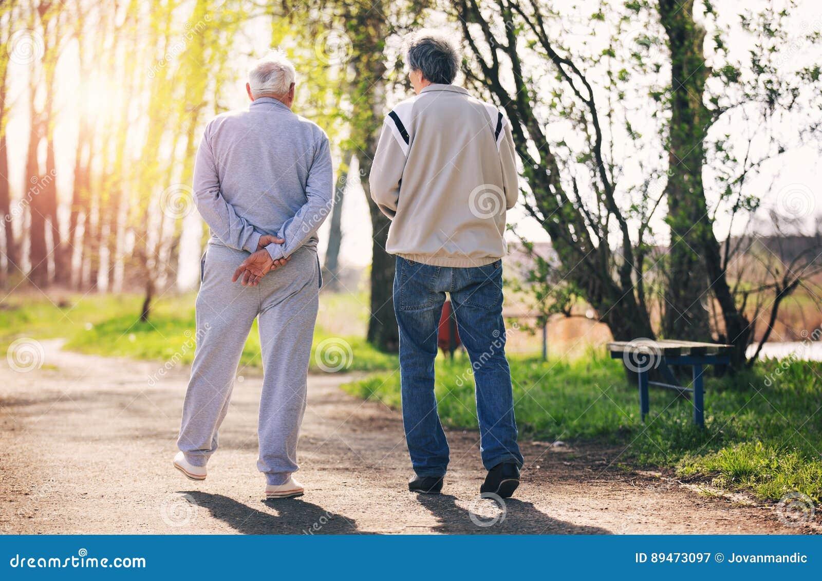 Ansicht von hinten eines erwachsenen Sohns, der mit seinem älteren Vater geht