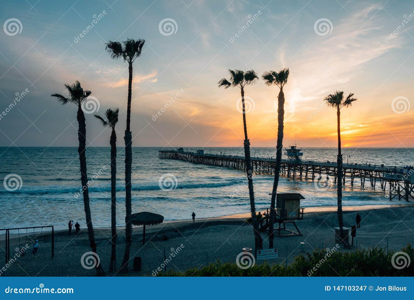 Ansicht von Palmen, von Strand und von Pier bei Sonnenuntergang, in San Clemente, County, Kalifornien