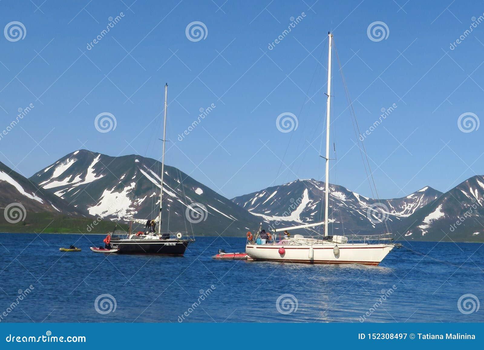 Ansicht von zwei Yachten unter den weißen und schwarzen Segeln konkurrieren im Teamsegelnereignis Nordsee, blauer Himmel und Berg