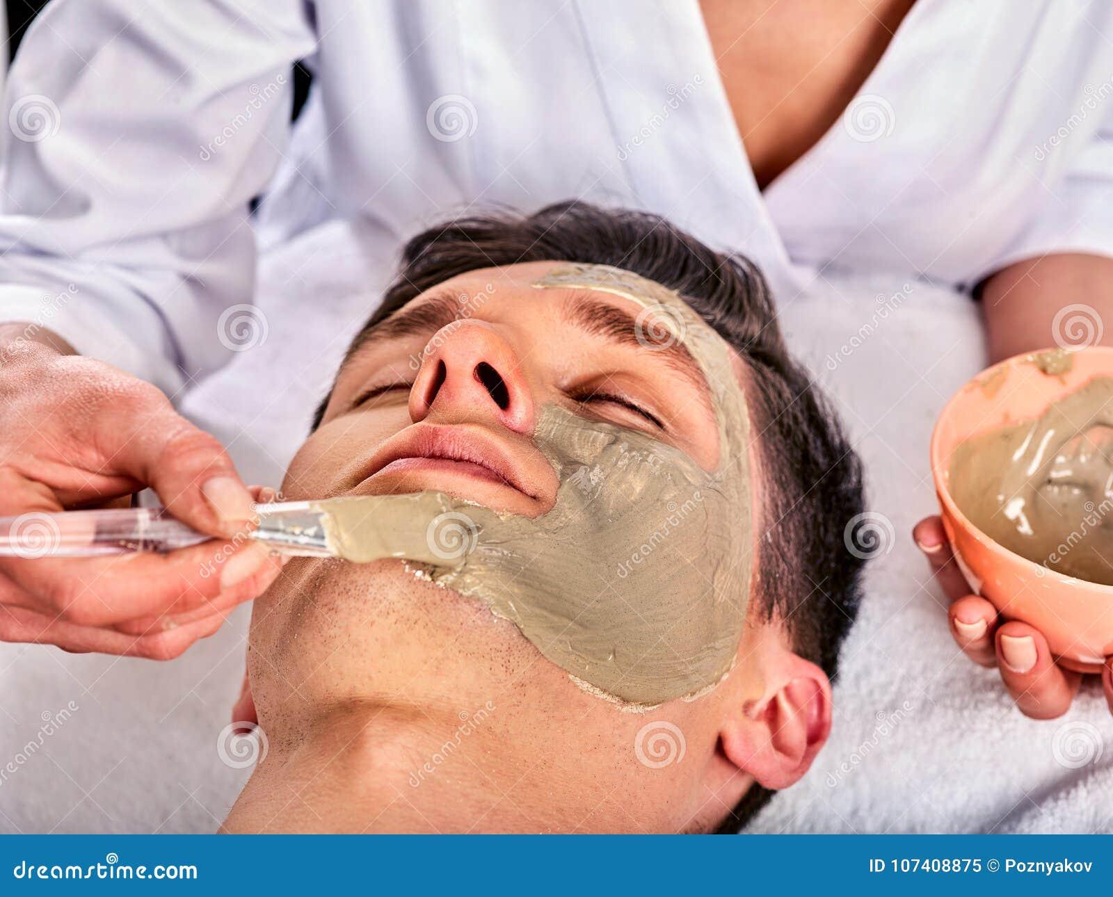 Ansikts- maskering för gyttja av kvinnan i brunnsortsalong Närbild av en ung kvinna som får Spa behandling