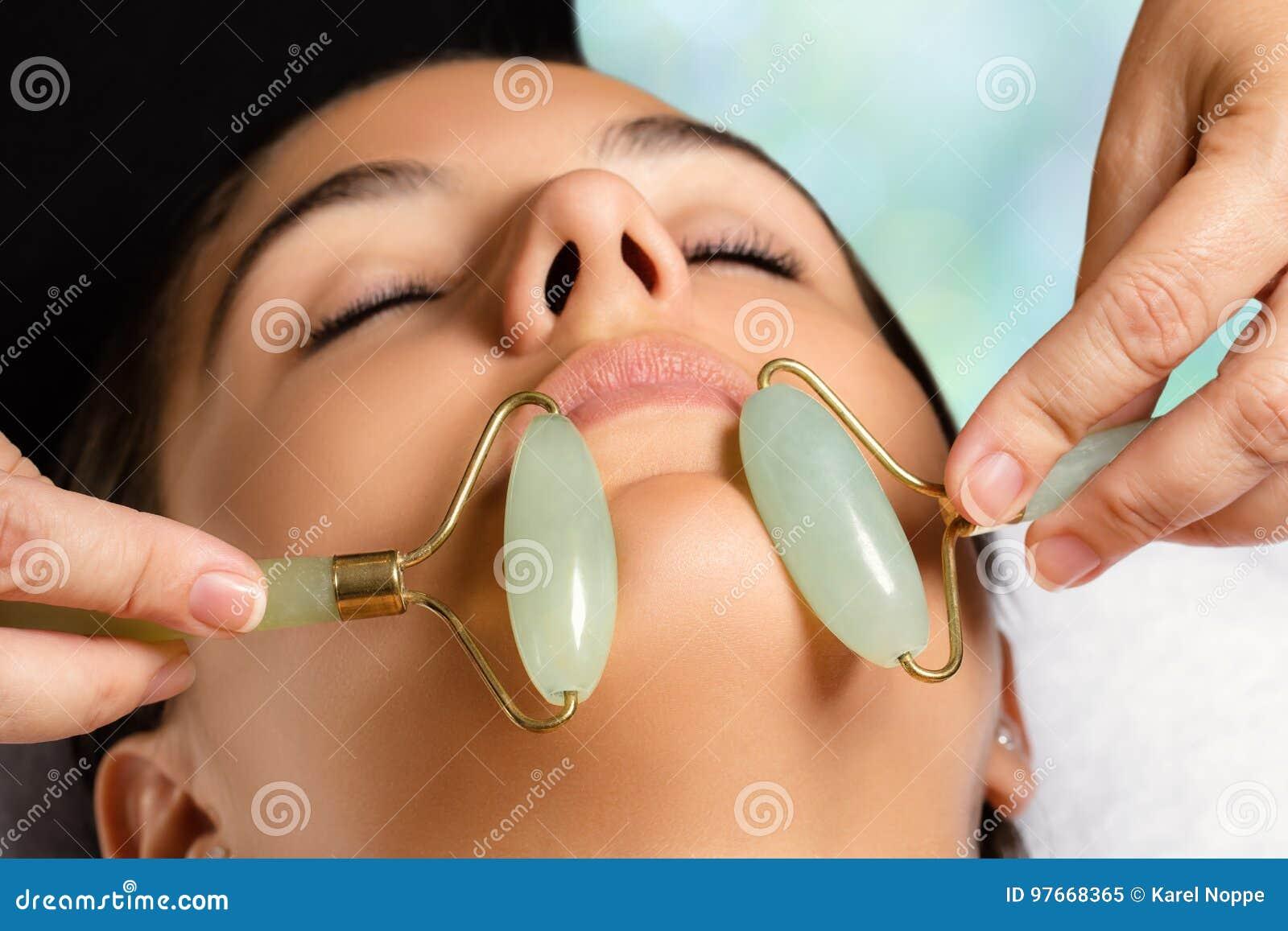 Ansikts- skönhetbehandling med jaderullar