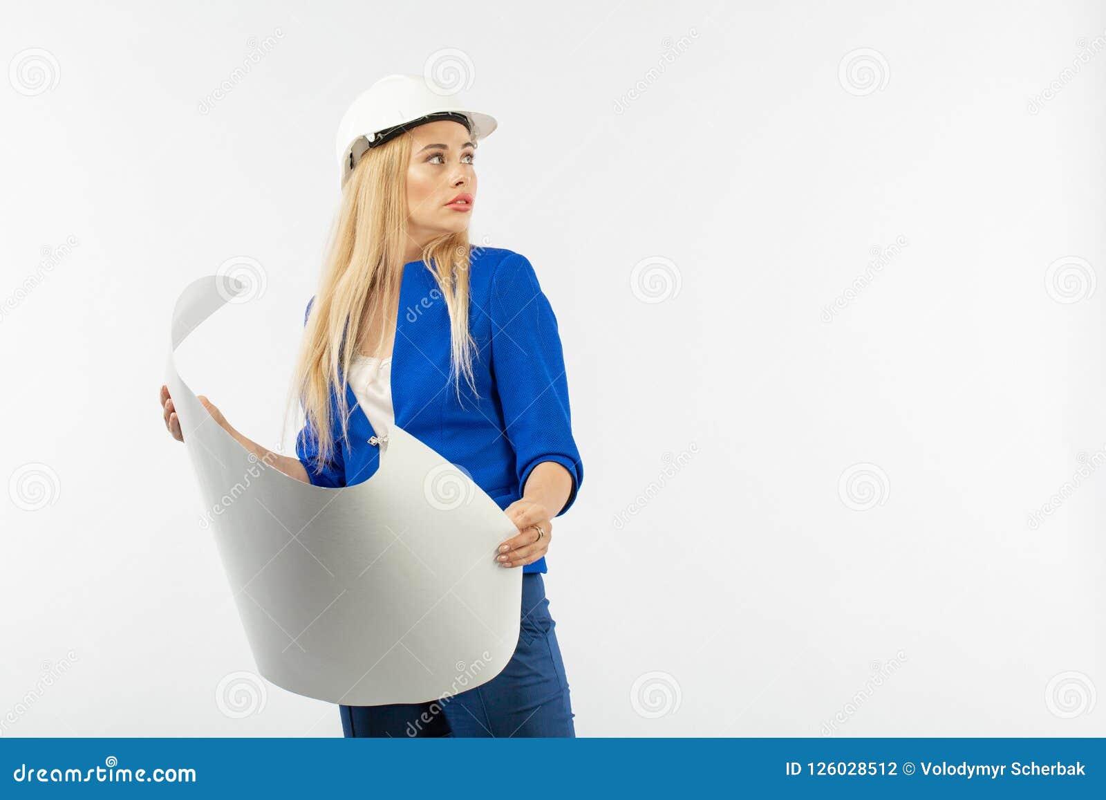 Anställdkvinna i dräktanseende i hjälm med pappers- dokument