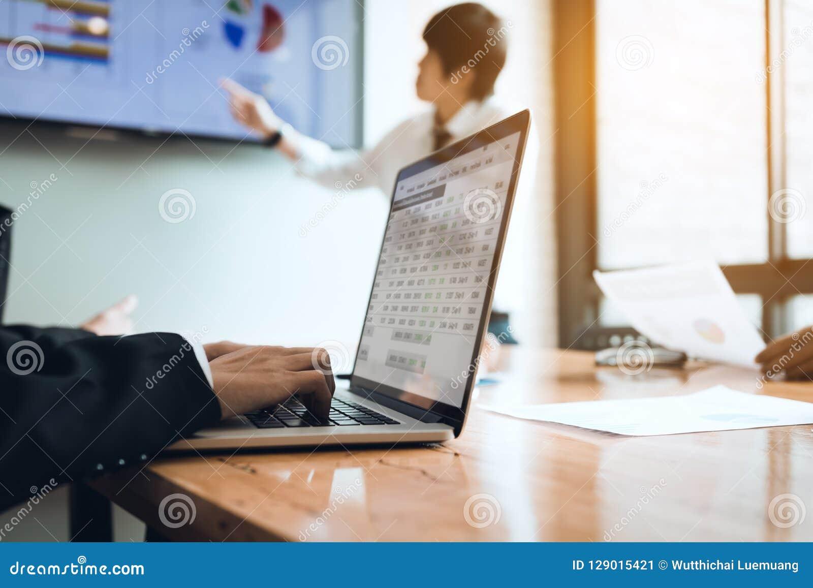 Anställdmöte som arbetar på skrivbordet och använder datorbärbara datorn på th