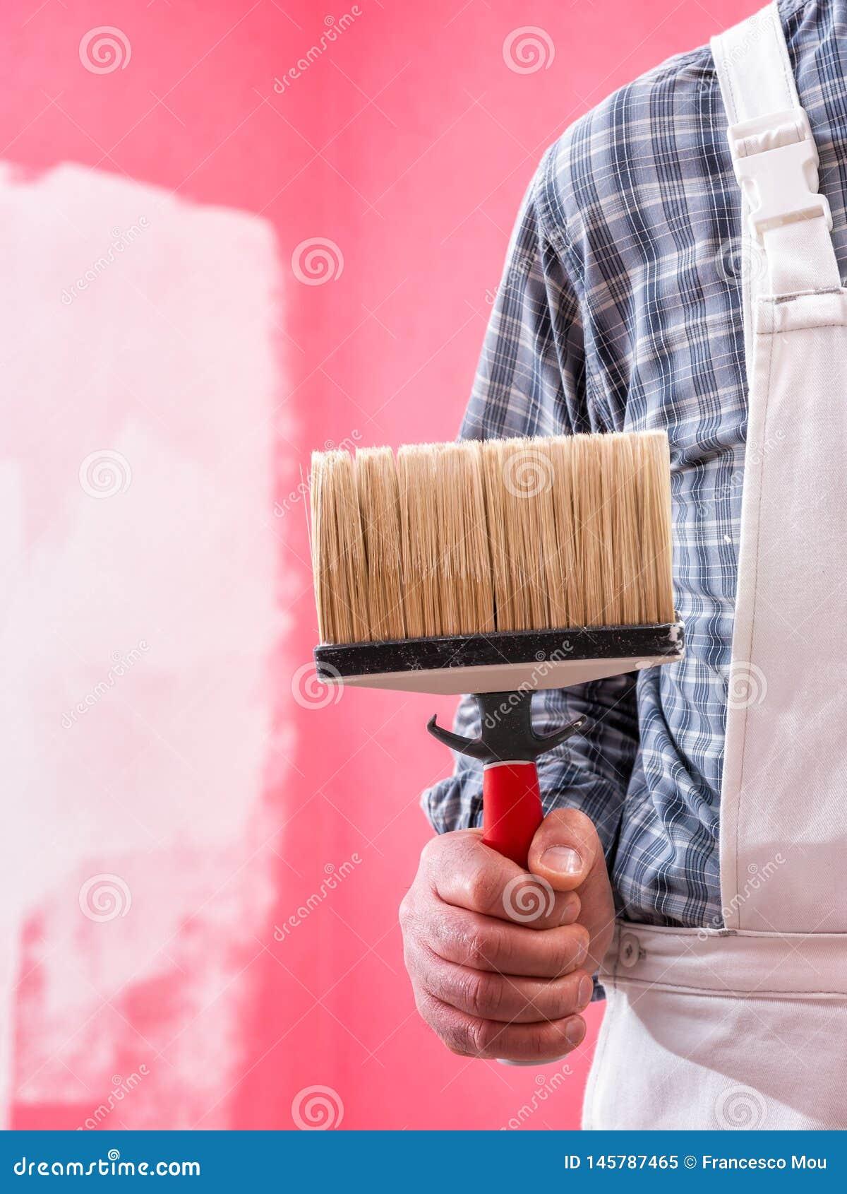 Anstreicherarbeitskraft mit Arbeitswerkzeugen Ziegelsteine, die drau?en legen