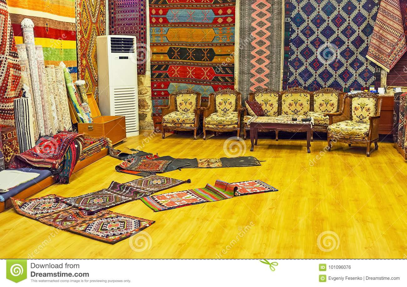 73c03bce65 ANTALYA, TURKEY - MAY 12, 2017: Interior of carpet store with the rolls of  different sized carpets and antique hand knotted camel saddle bags on the  floor, ...