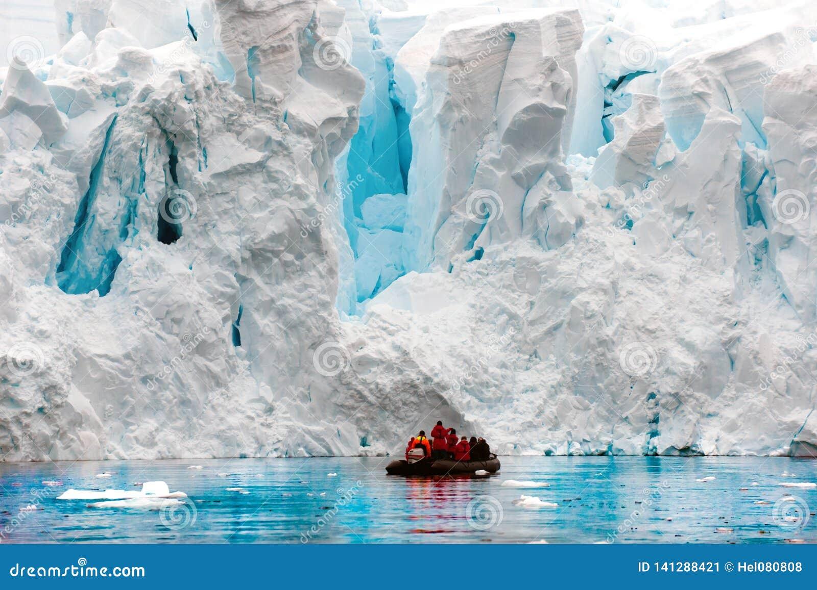 Glacier calving in Antarctic, people in Zodiac in front of escarpment of glacier