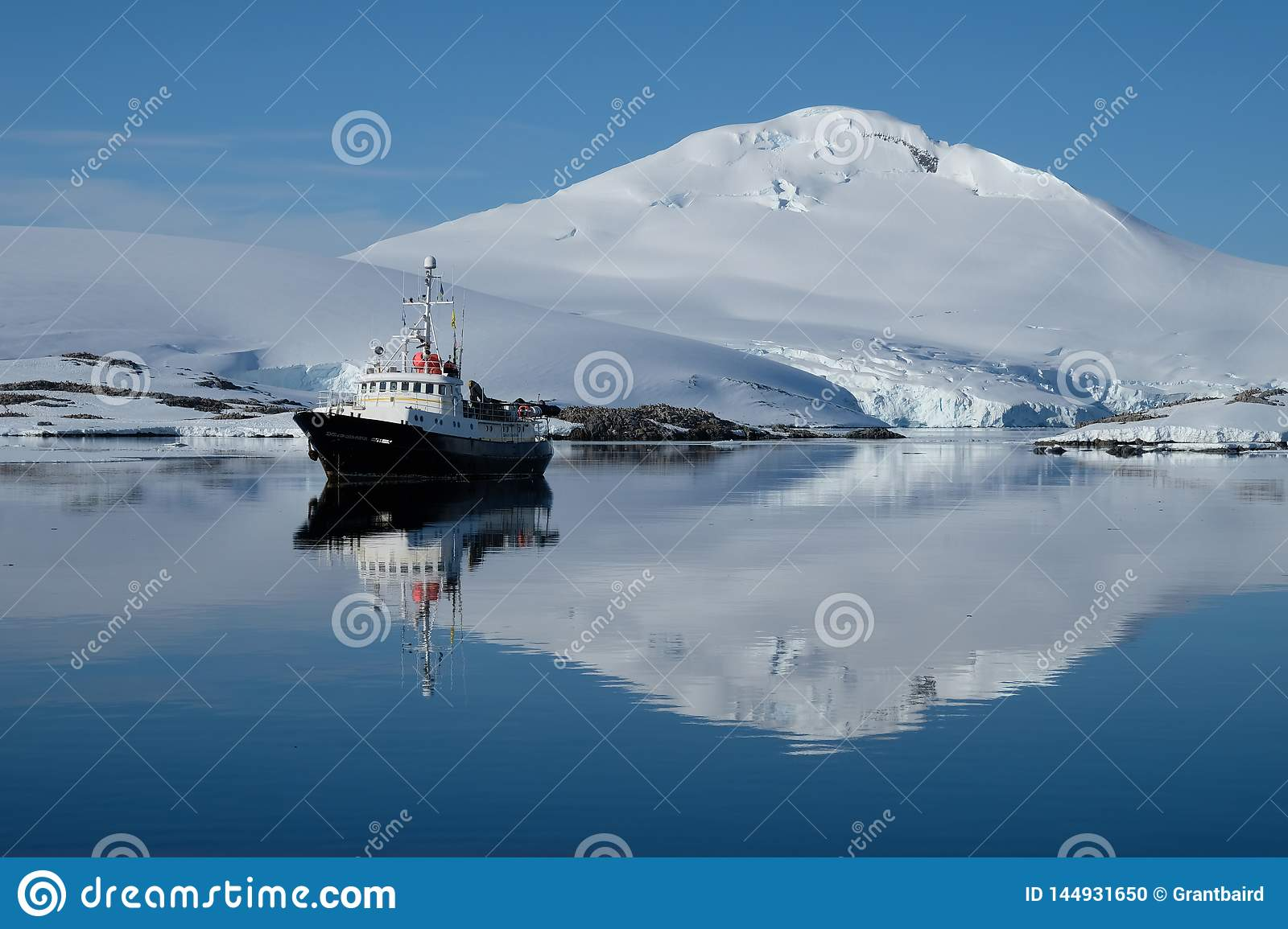 Antarctica boat ripples in a mirror blue bay beneath white snow capped mountain