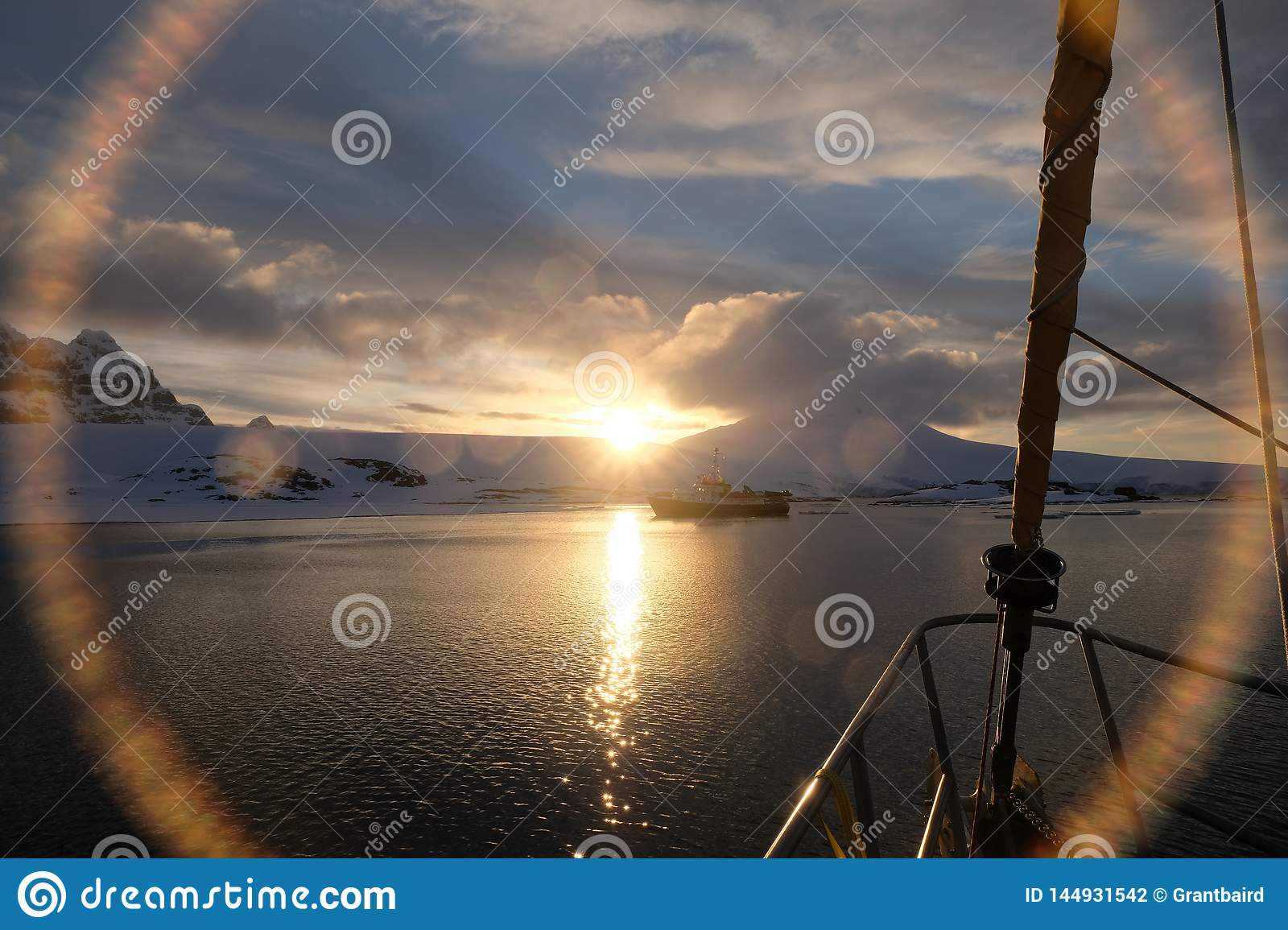 Antarctica calm midnight sunset lens flare from sailboat