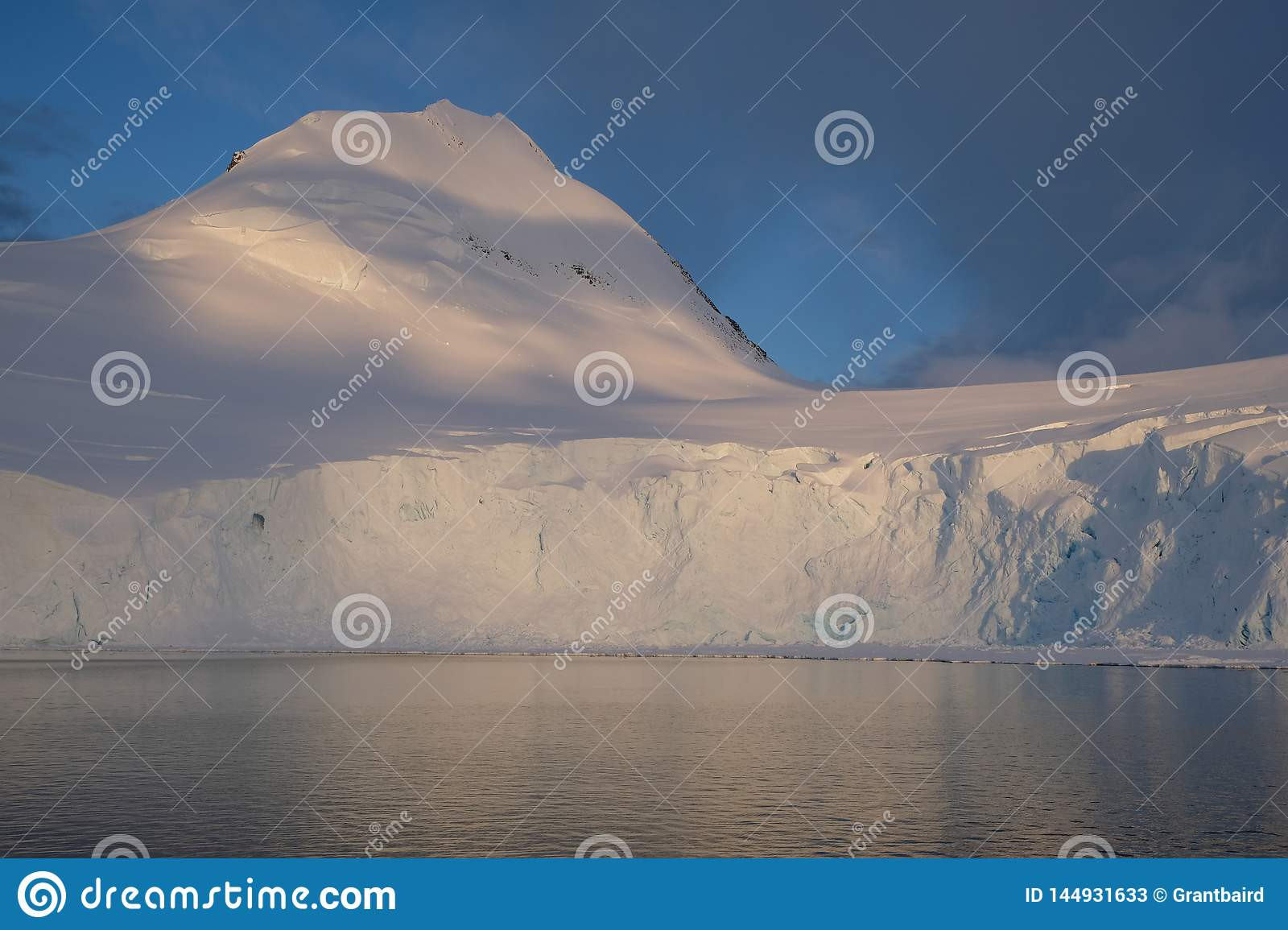 Antarctica calm midnight sunset on snowy mountain
