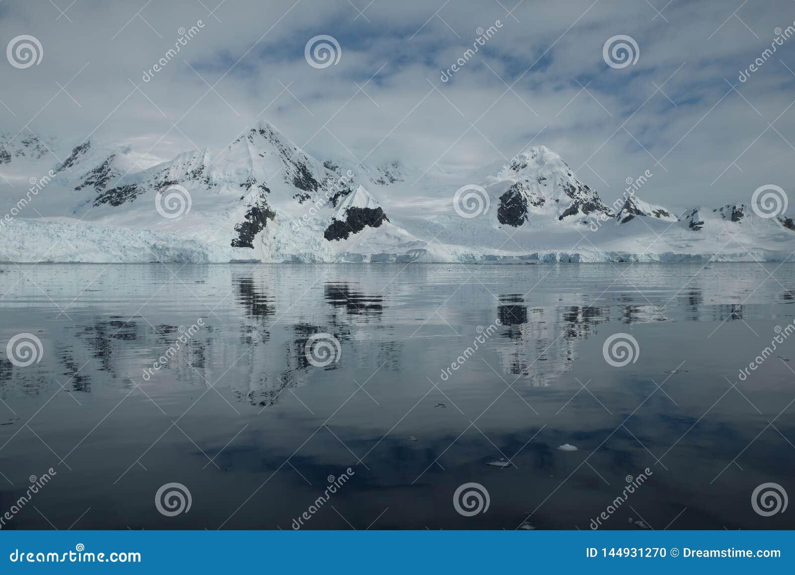 Antarctica glacial mountains reflecting in the mirror bay