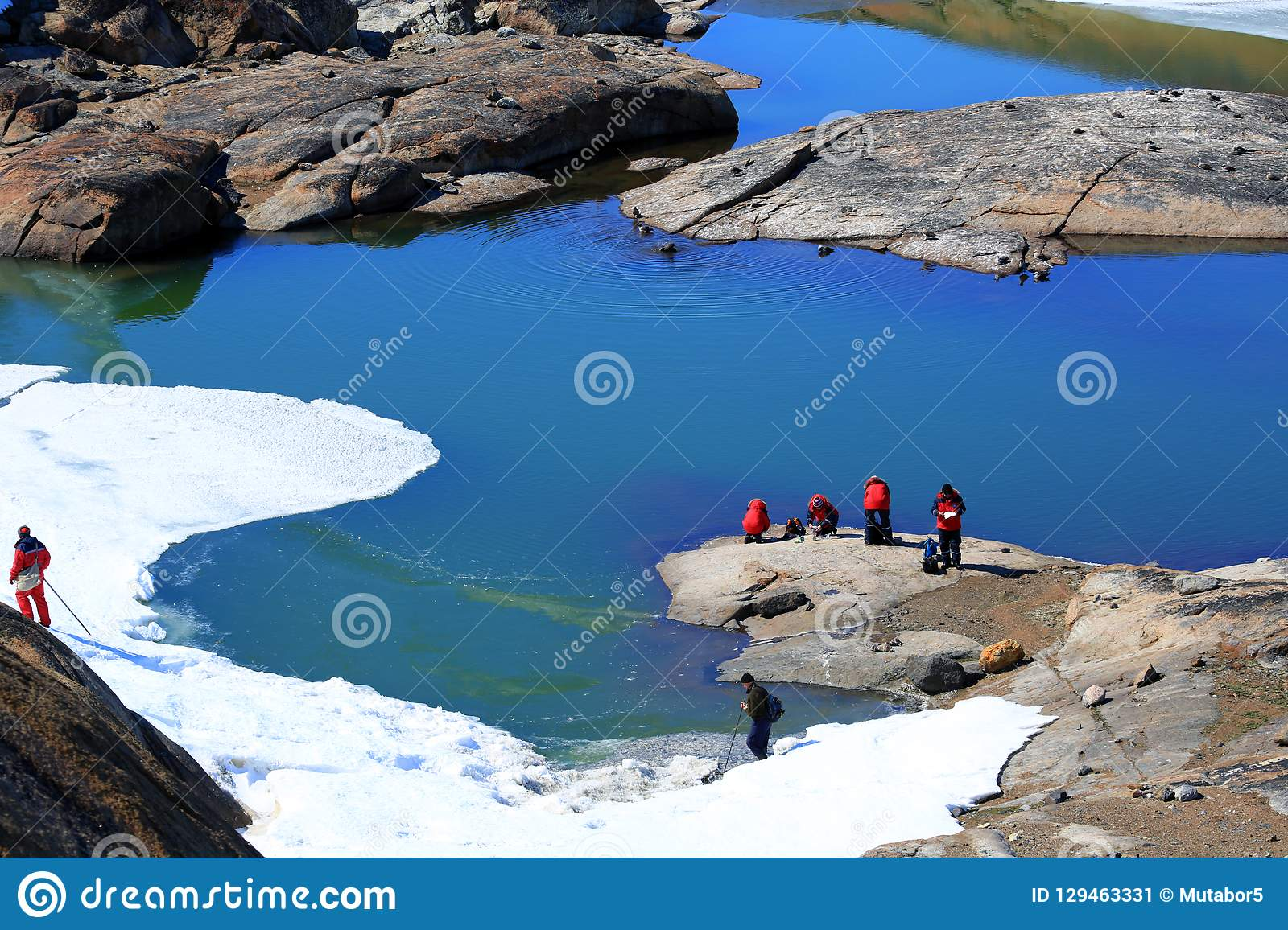 People, scientists, researchers are on the mountain of stone. Near the shore of the ocean and icebergs.