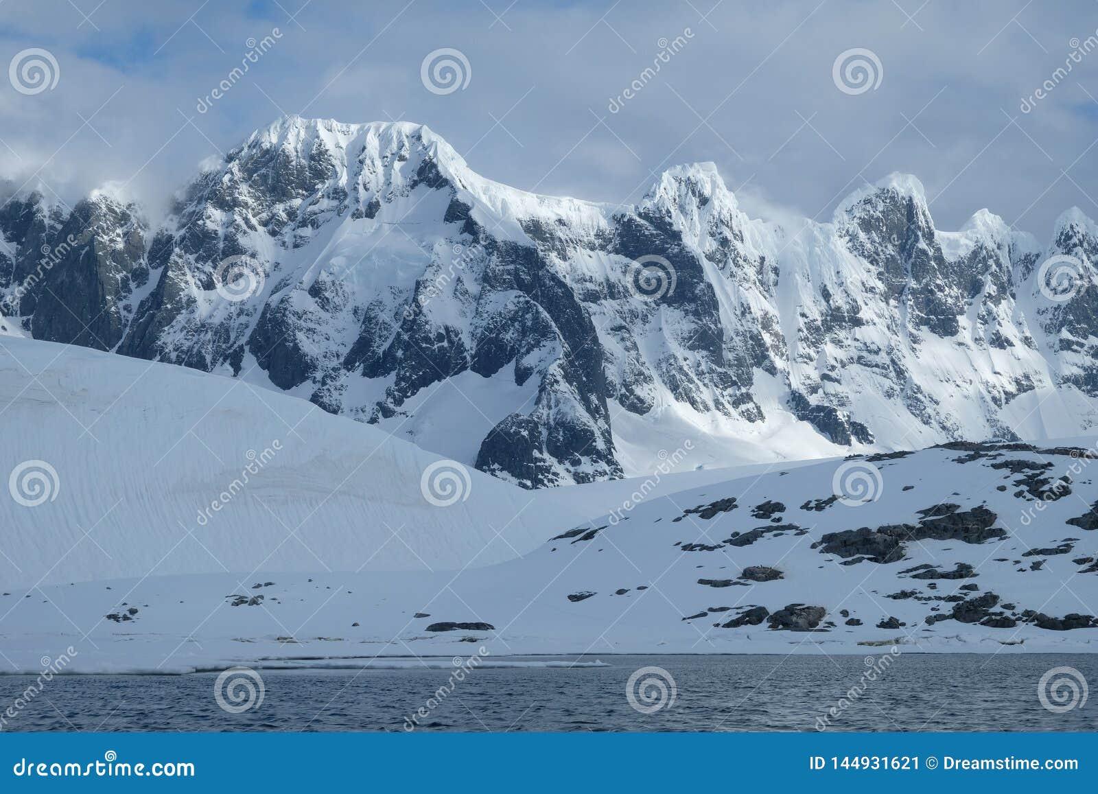 Antarctica szczerbił śnieżne góry w ranku świetle na chmurnym dniu