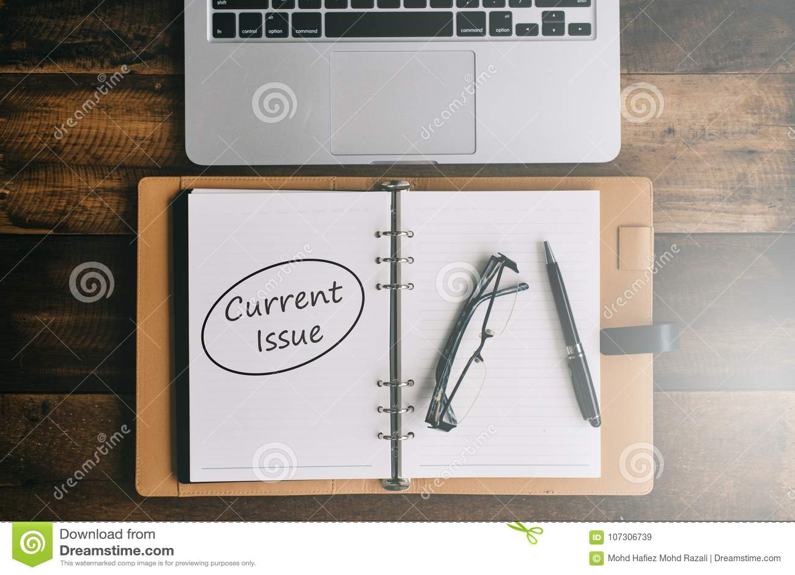 Anteckningsbok, bärbar dator, penna och anblickar på en trätabell med ord för AKTUELLA FRÅGOR