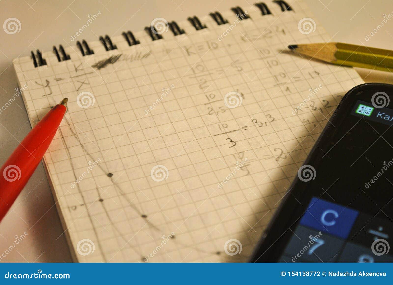 Anteckningsbok formler, matematiska diagram, läxa, mobiltelefon