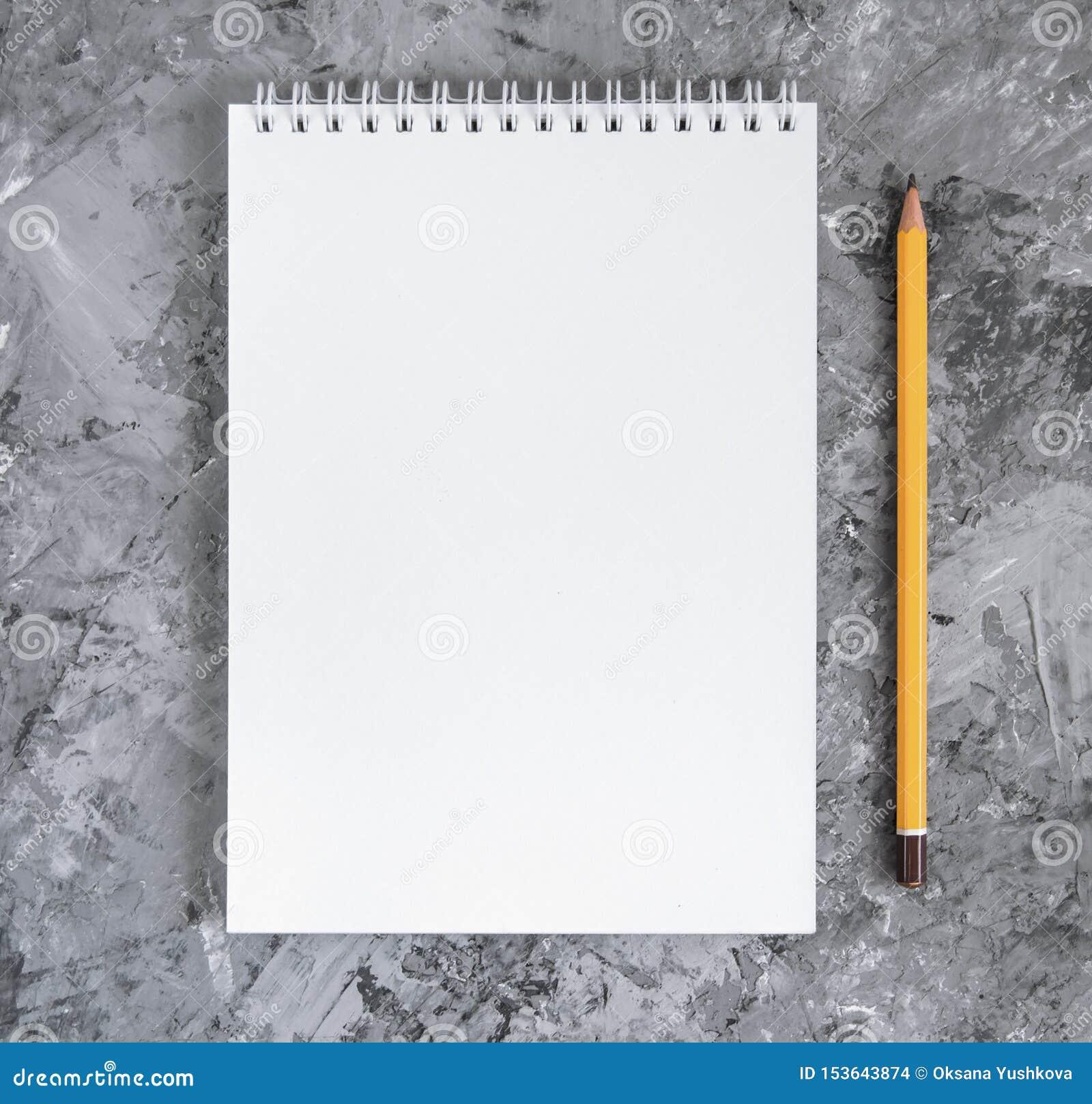 Anteckningsbok med en blyertspenna på en konkret bakgrund
