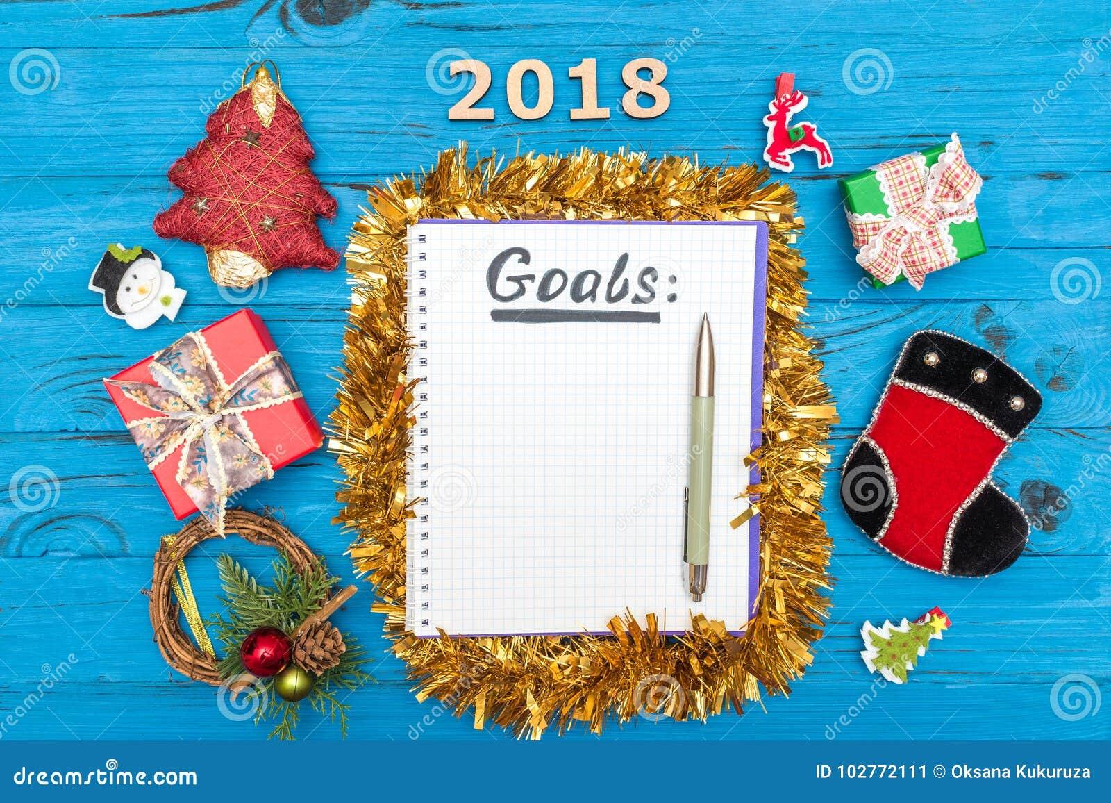 Anteckningsbok med mål för nya år för 2018 med en penna och nummer 2018, gåvaaskar och prydnader för nytt år på en träblått