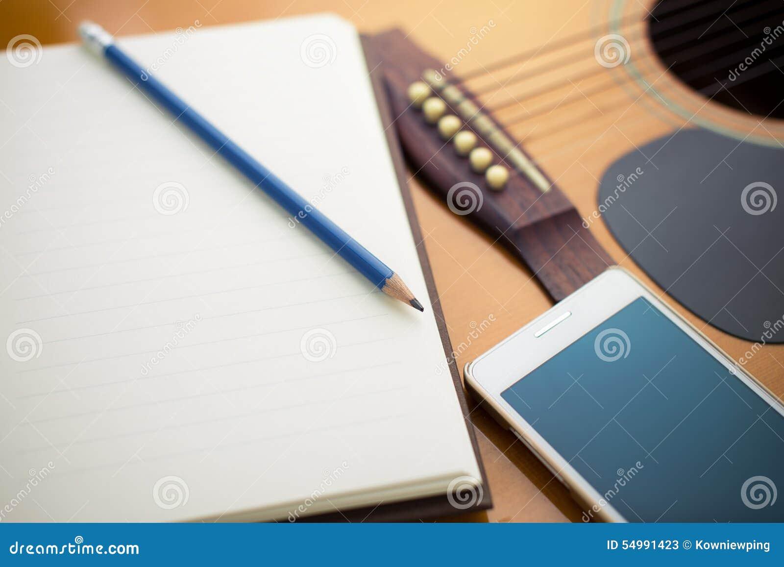 Anteckningsbok och blyertspenna på gitarren