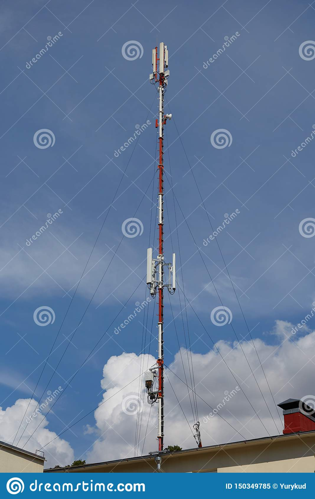 Antena da rede de rádio do celular no sinal de transmissão de construção do telhado sobre a cidade