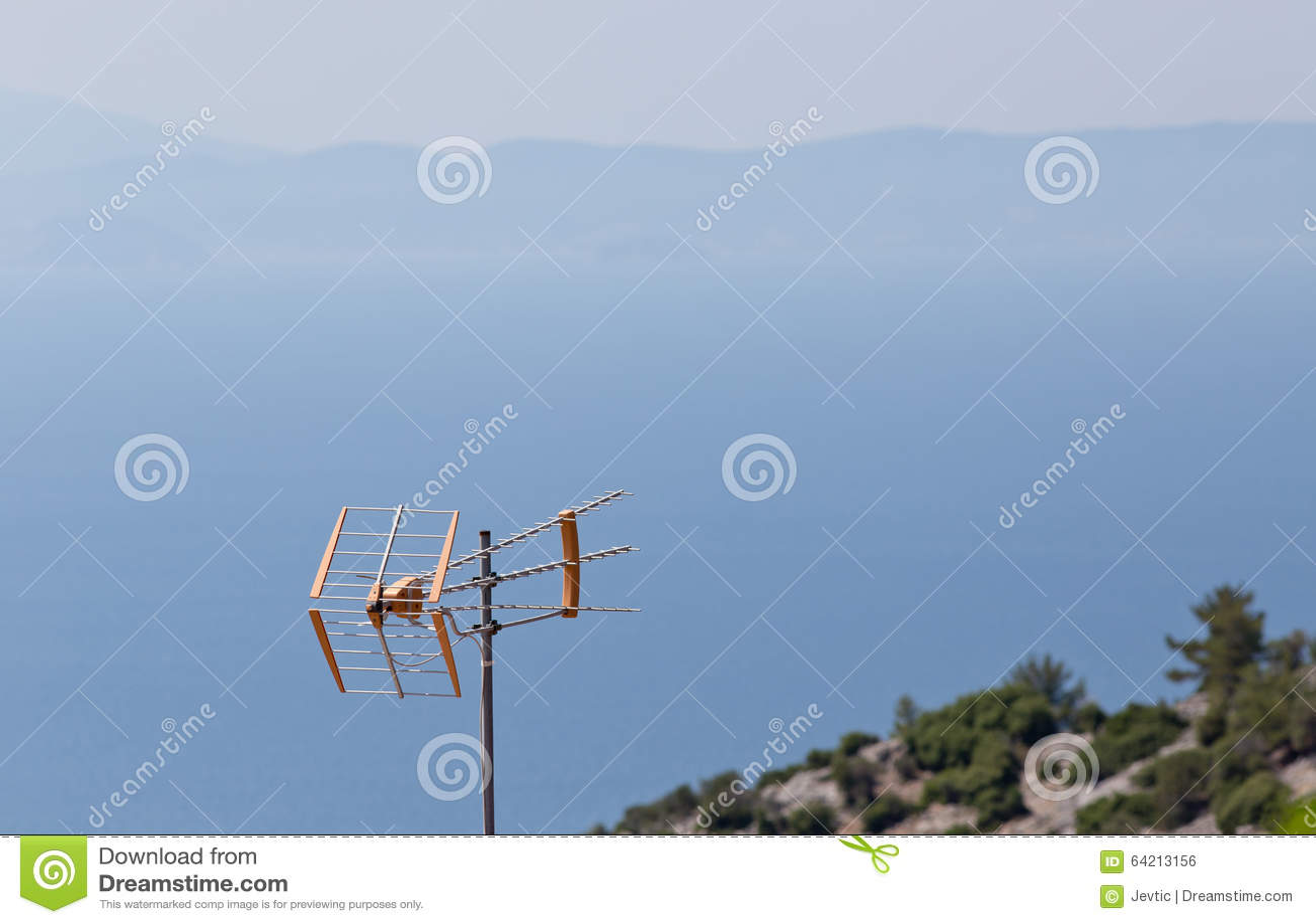 Antena de TV con las montañas y playa en fondo