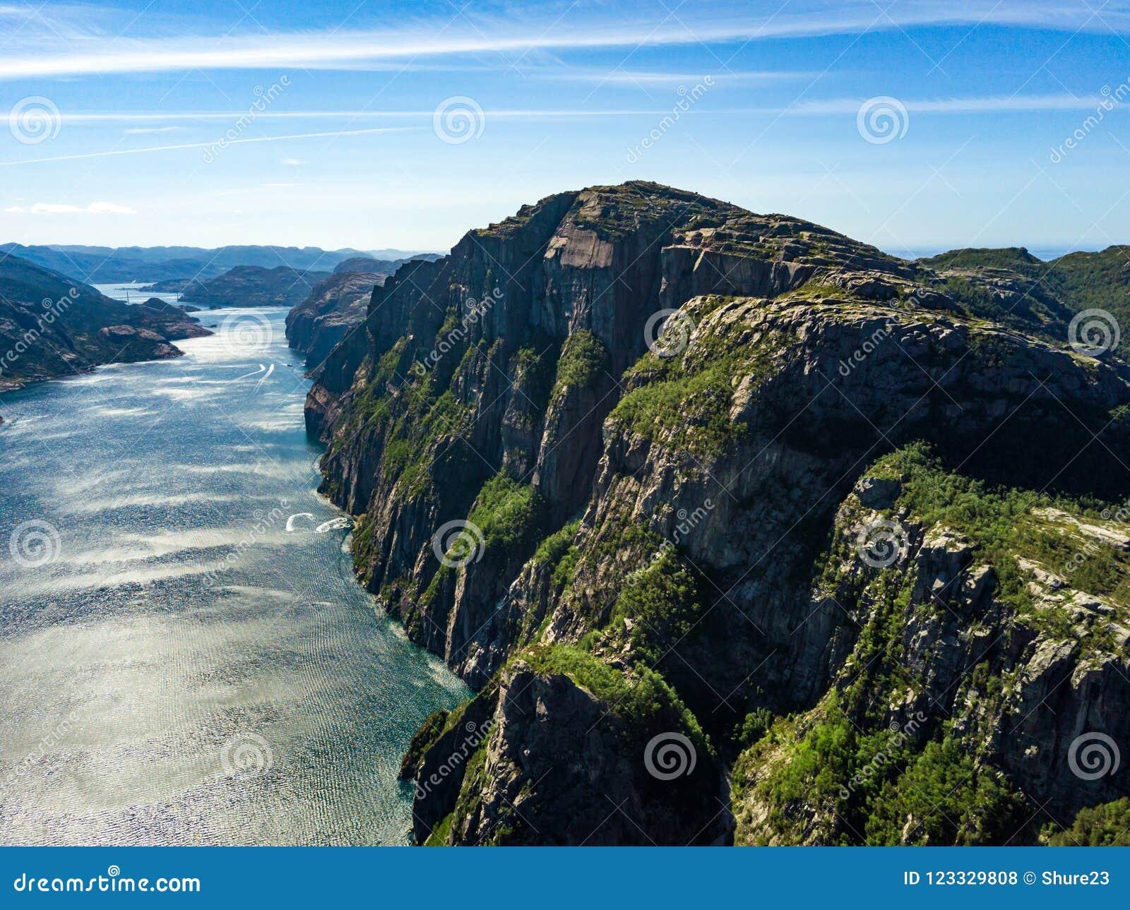 Antena do ponto de caminhada famoso em Noruega - rocha Preikestolen do púlpito E Lyse o fiorde abaixo