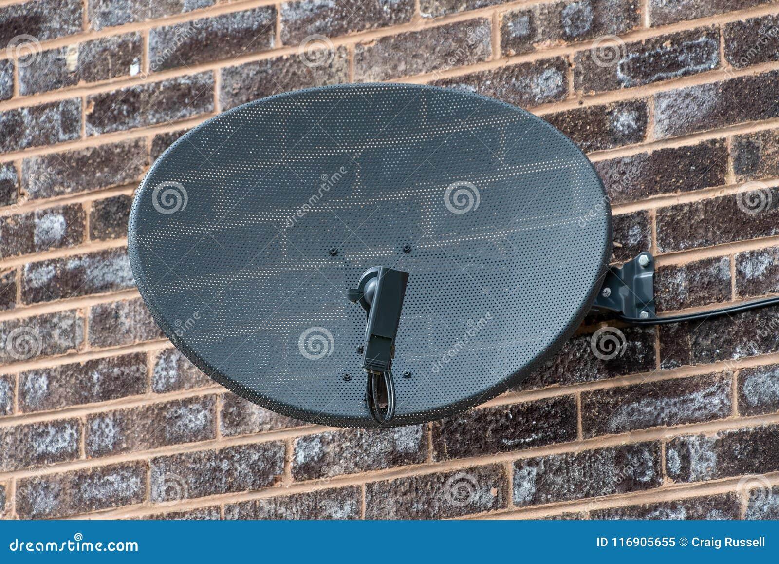 Antena parabólica da tevê em uma parede de tijolo