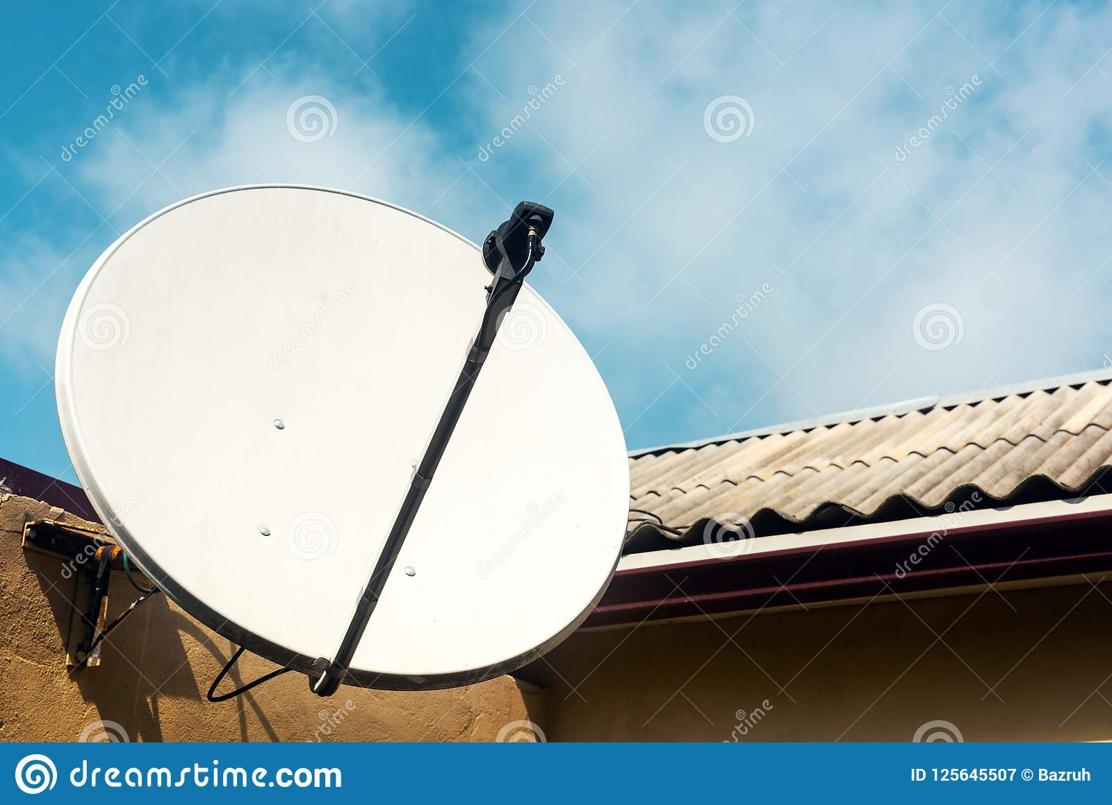 Antena parabólica na parede de uma casa de campo