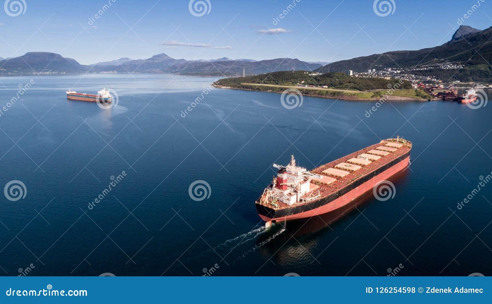 Antena strzał ładunku statek na otwartym morzu z innymi górami w tle i statkiem