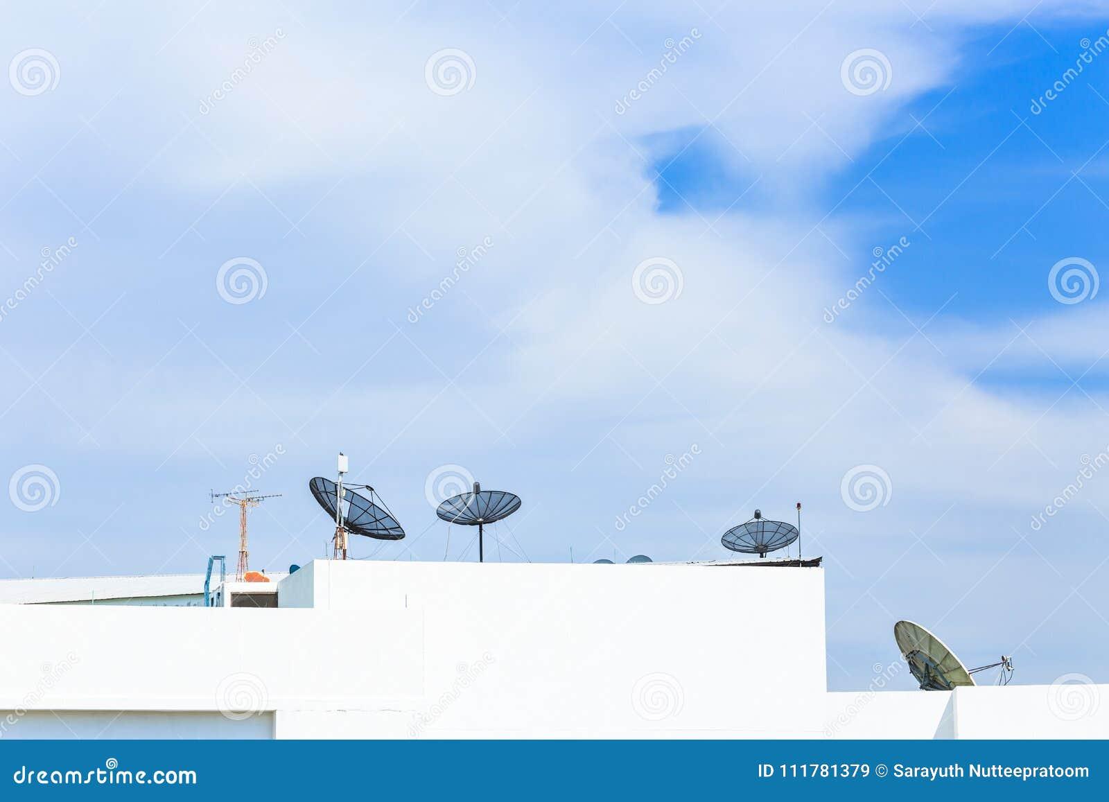 Antenn för satellit- maträtt överst av byggnaden i stadsområde på n