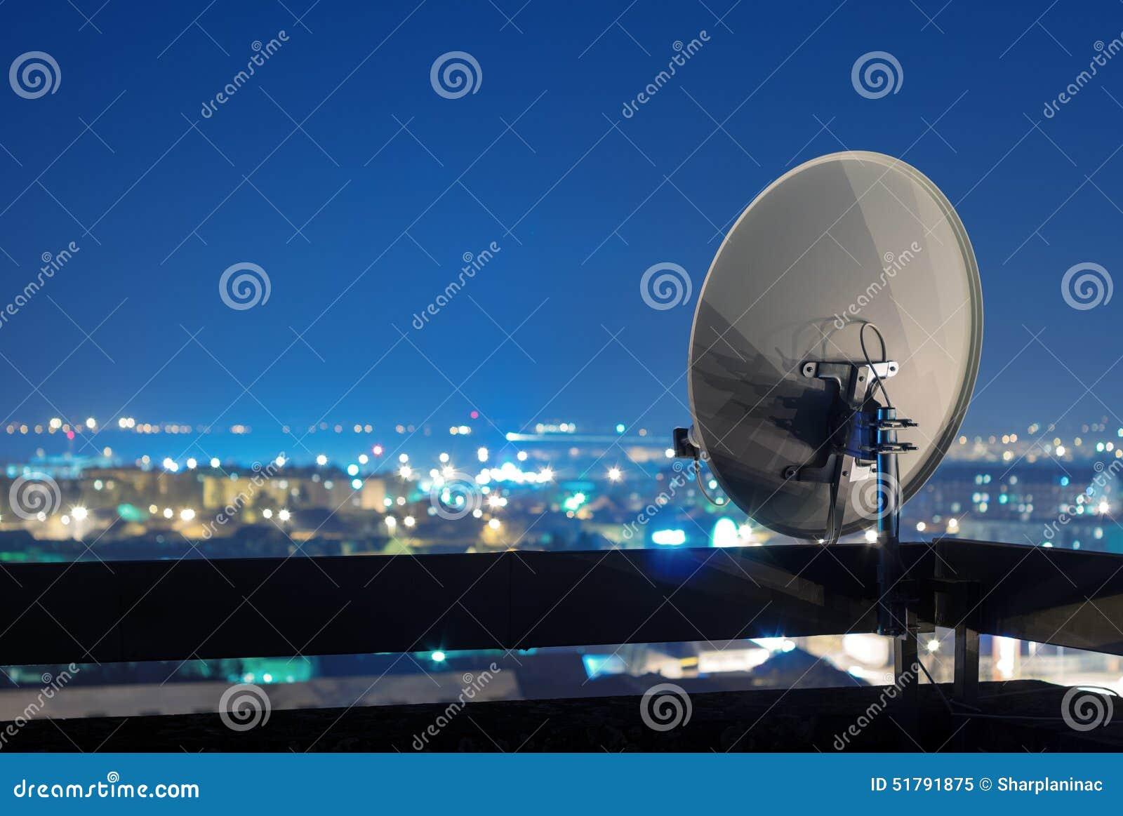 Antenn för satellit- maträtt överst av byggnaden på natten