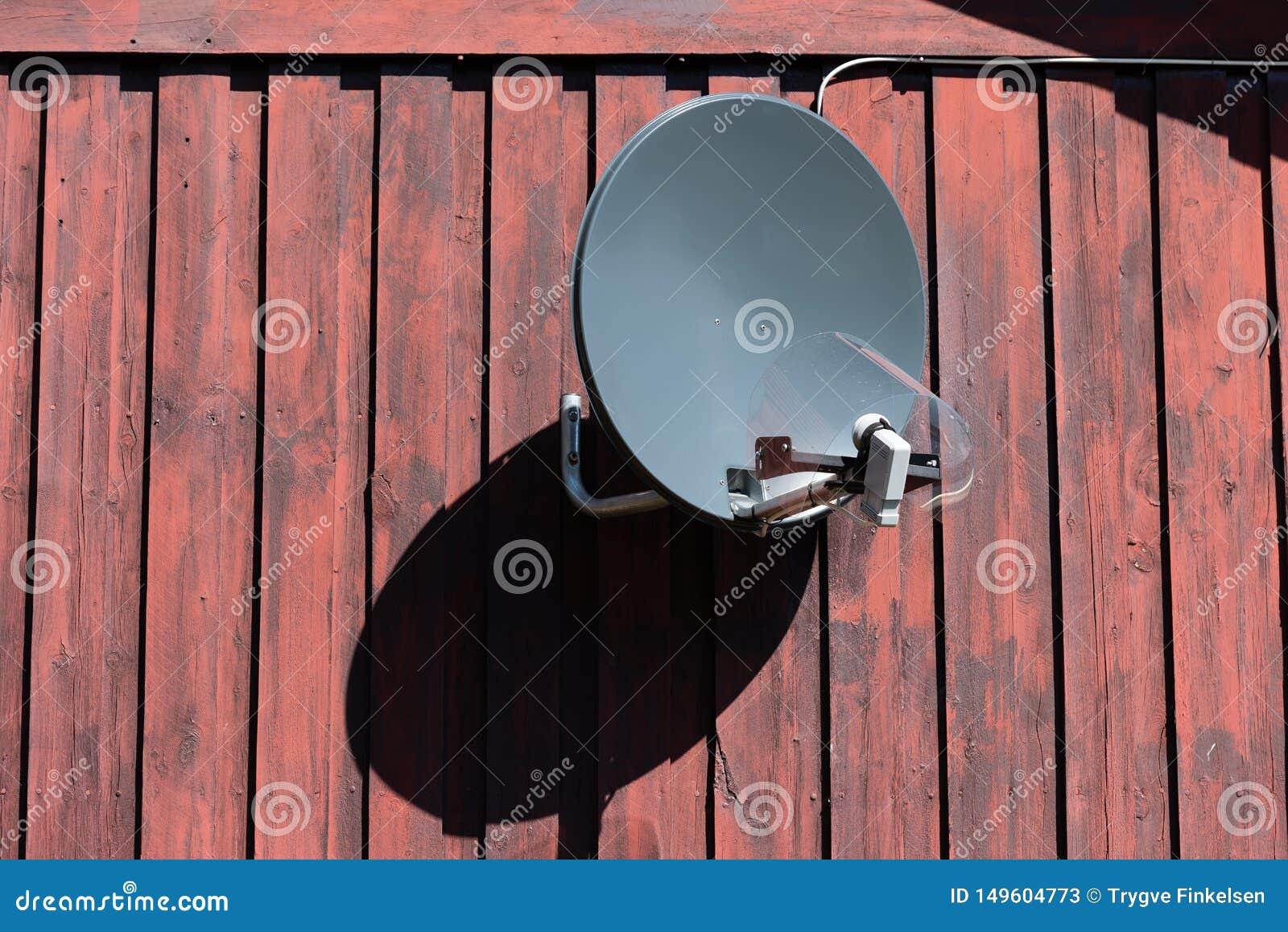 Antenna parabolica su una vecchia parete di legno