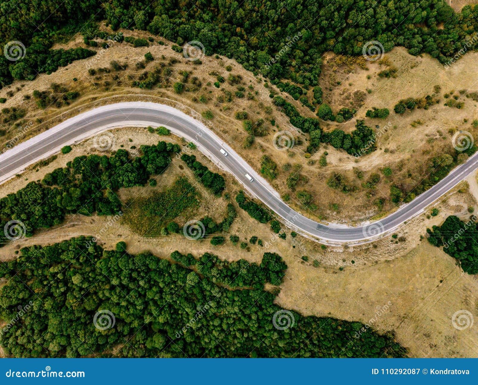 Antenne über Ansicht einer ländlichen Landschaft mit einem curvy Straßenlauf durch ihn in Griechenland
