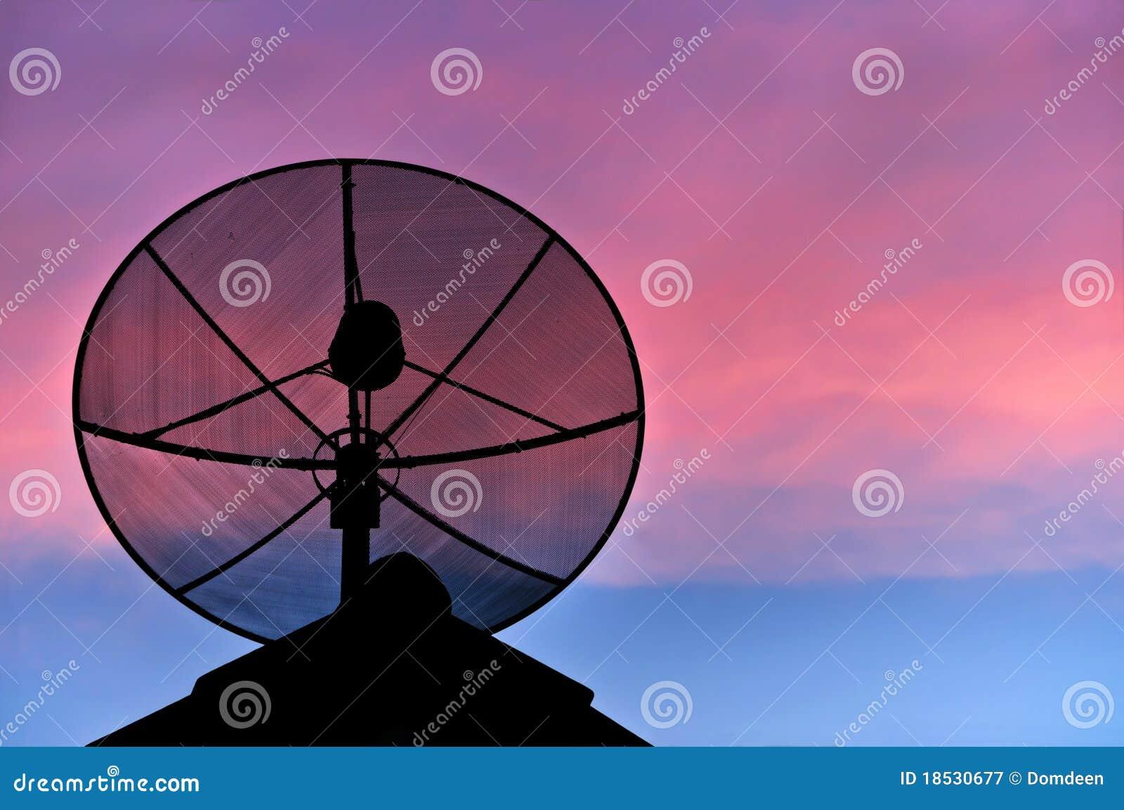 Antenne parabolique sur le toit en ciel de soirée.