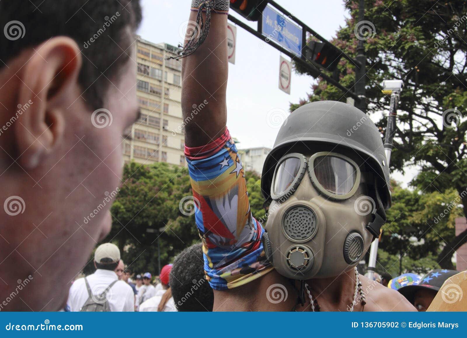 Anti vestir dos protestadores de Nicolas Maduro lança gás lacrimôgeneo a máscara durante as manifestações em massa que transforma