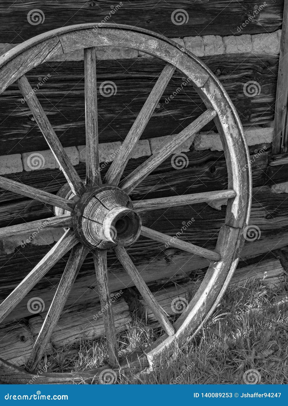 Antiek houten wagenwiel tegen houten schuur