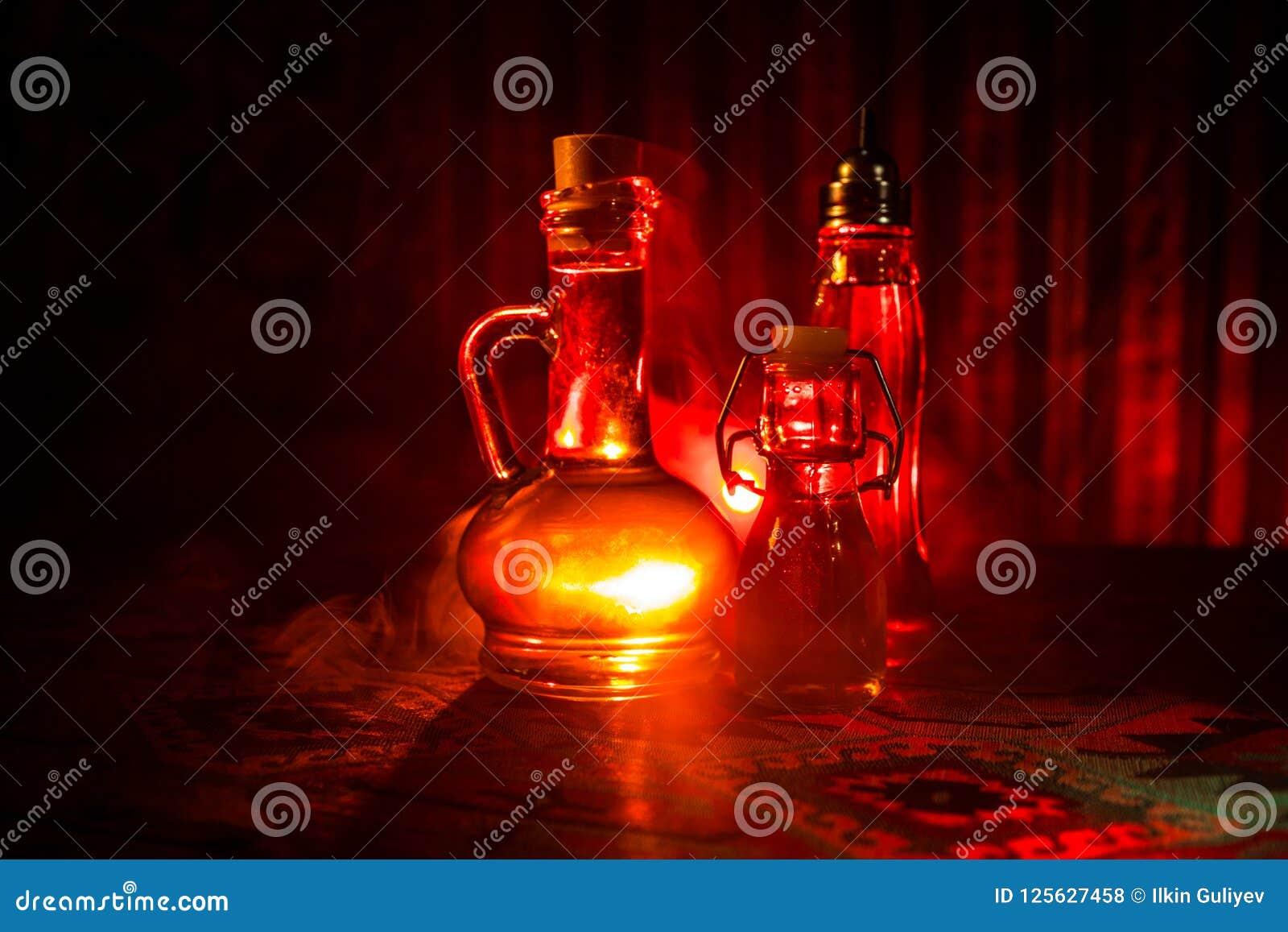 Antieke en uitstekende glasfles op donkere mistige achtergrond met licht Vergift of magisch vloeibaar concept