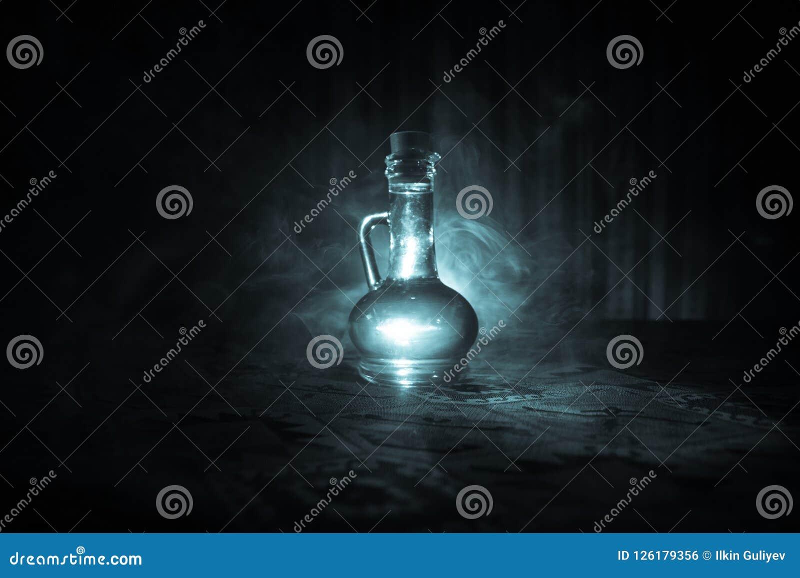 Antieke en uitstekende glasflessen op donkere mistige achtergrond met licht Vergift of magisch vloeibaar concept