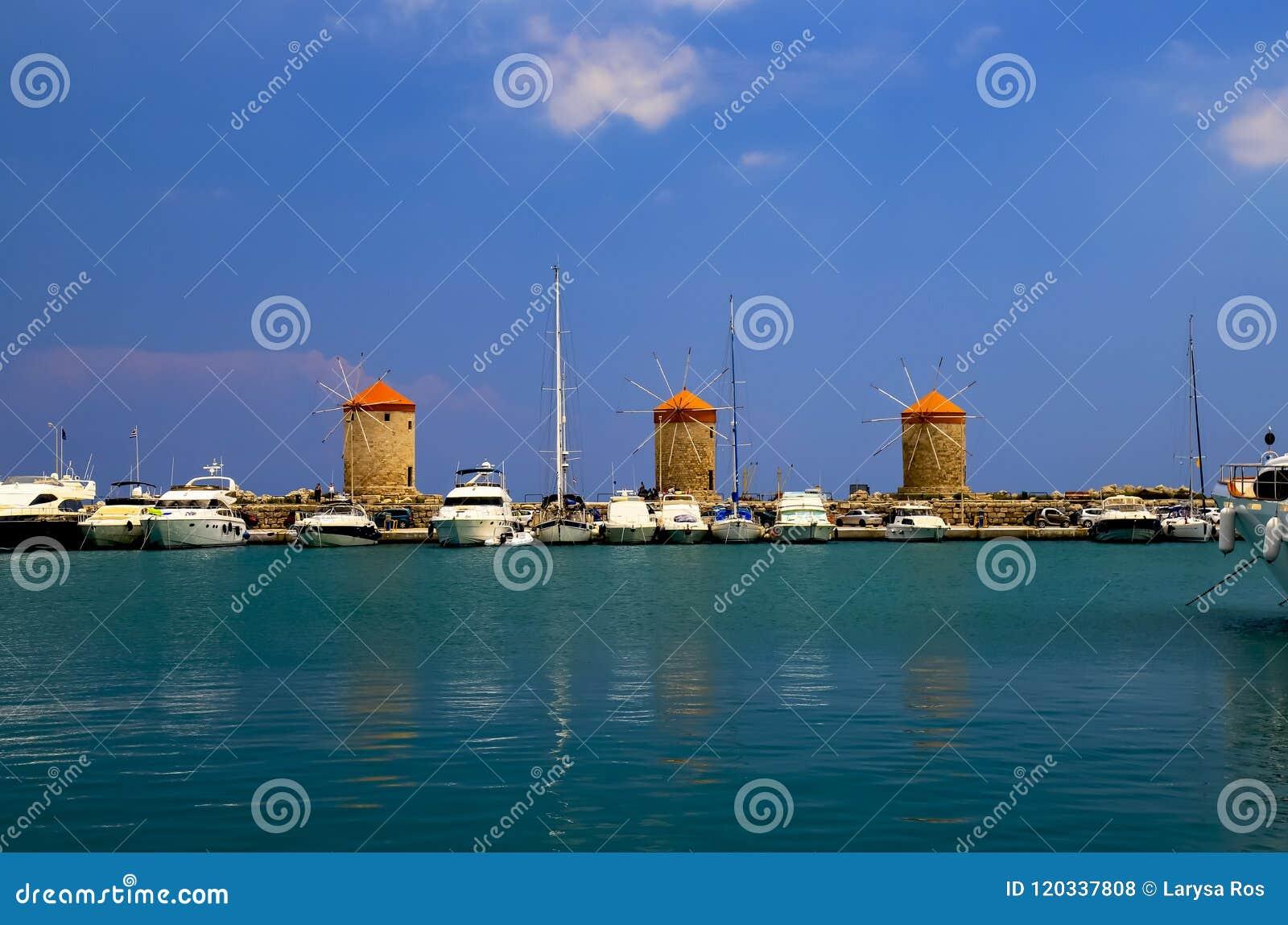 Antieke gele geeloranje molens in de haven van Mandraki, Rhodos, Griekenland