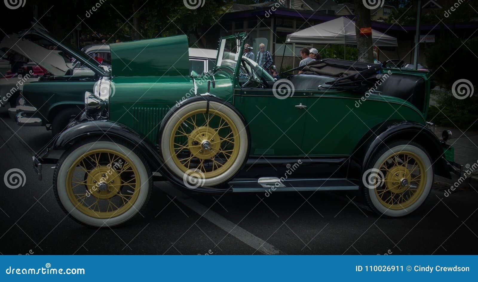 Antieke groene auto met de zetel in de laars