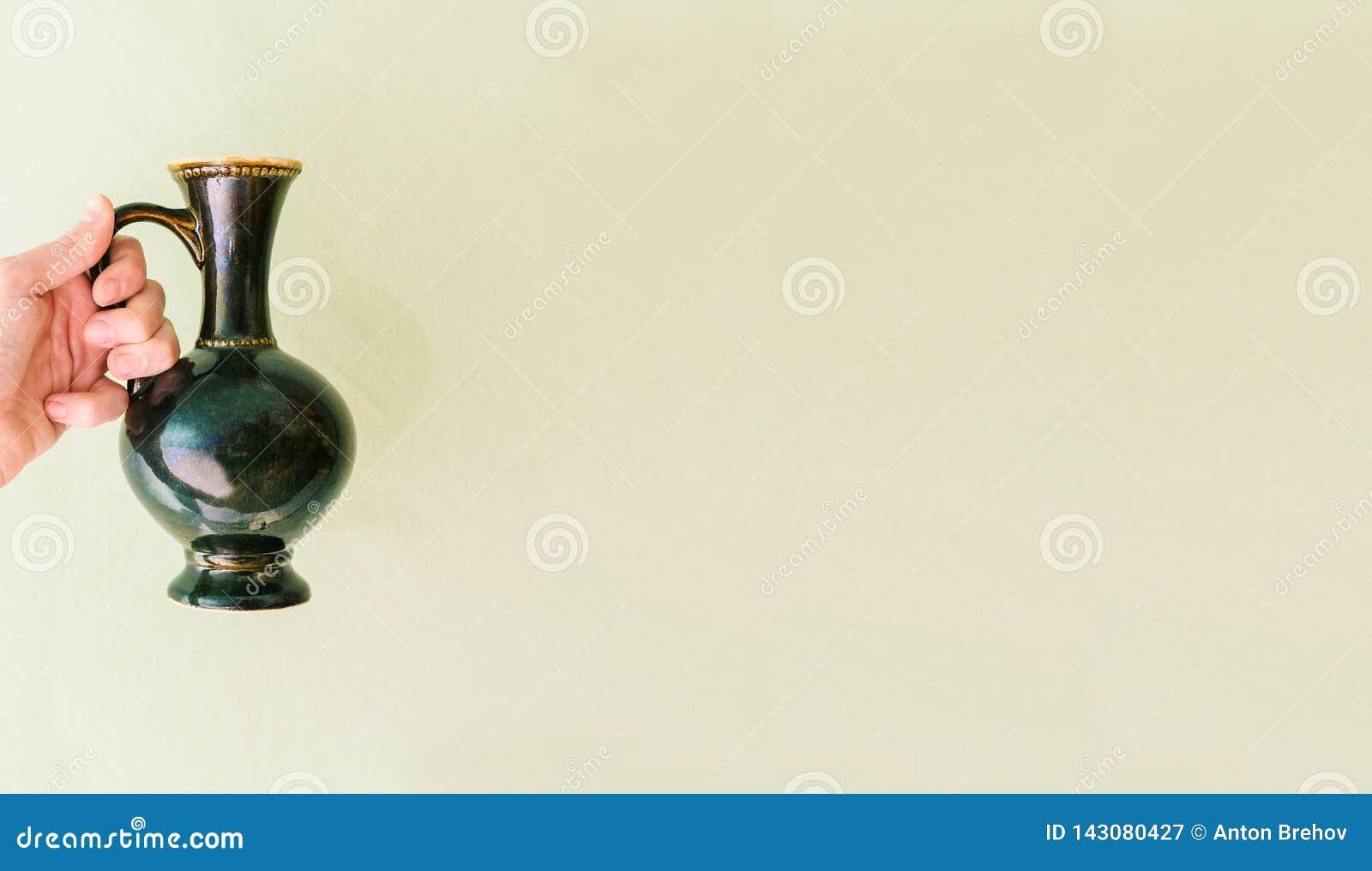 Antik vas i handen av en kvinna En kvinna rymmer en antikvitet på en grön bakgrund placera text