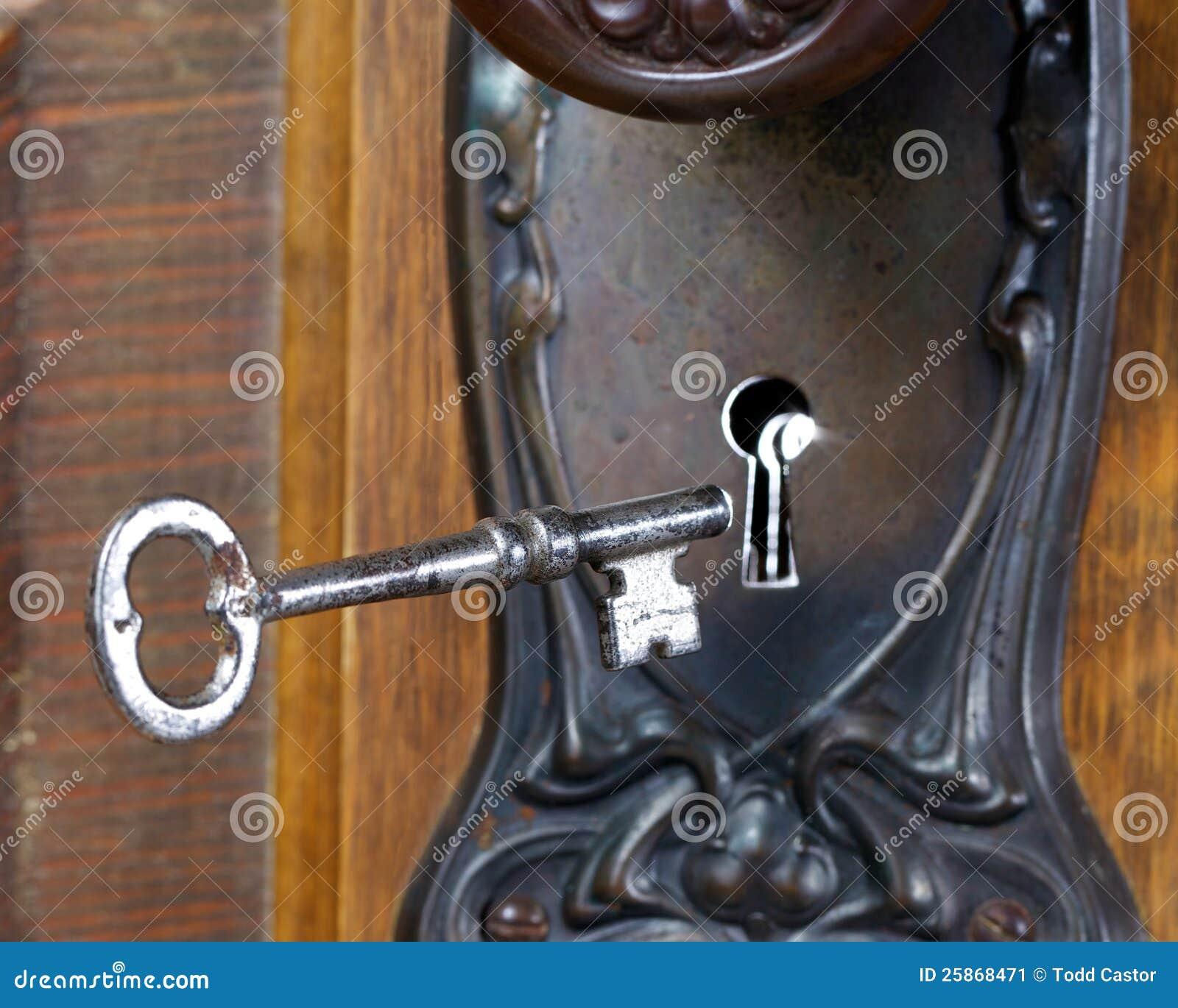 Antike Tür mit der skeleton Taste, die in Schlüsselloch einsteigt