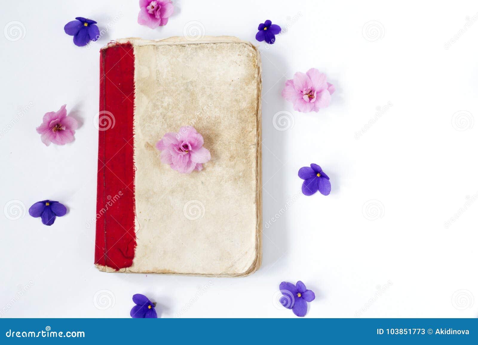 Antikes Papierbuch und Blumen auf weißem Hintergrund