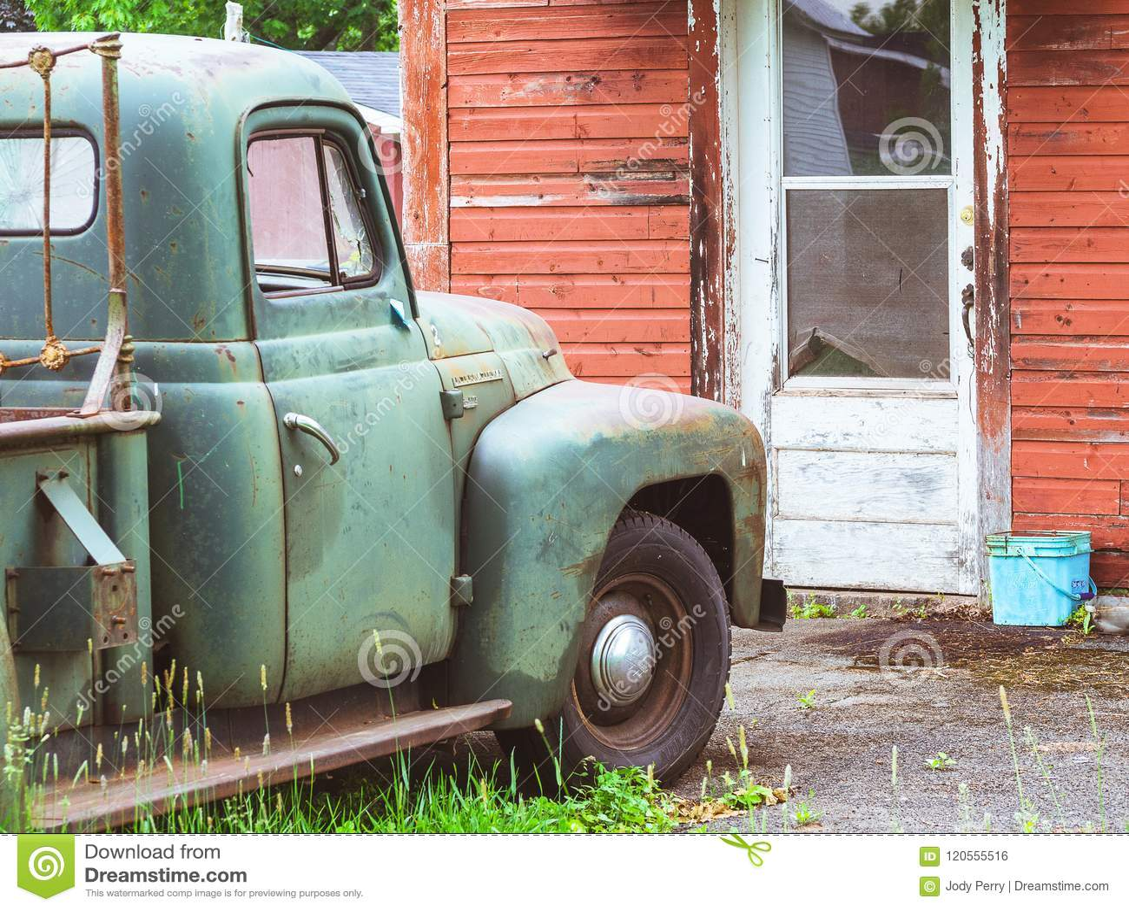 Antikviteten åldrades den gamla lastbilen framme av gammal riden ut byggnad