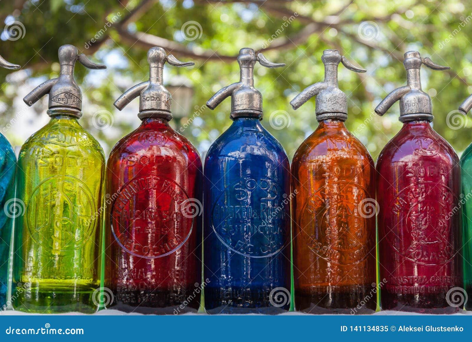 Antikviteten suger upp genom hävert ljusa flaskor, kulört exponeringsglas i loppmarknaden, Buenos Aires, Argentina