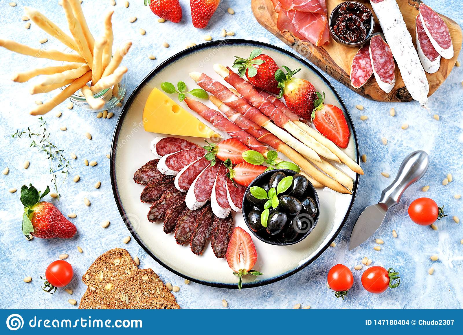 Antipasti snacks - sausage, homemade grissini with jamon, olives, strawberries, capers, cherry tomatoes, white wine, dried tomatoe