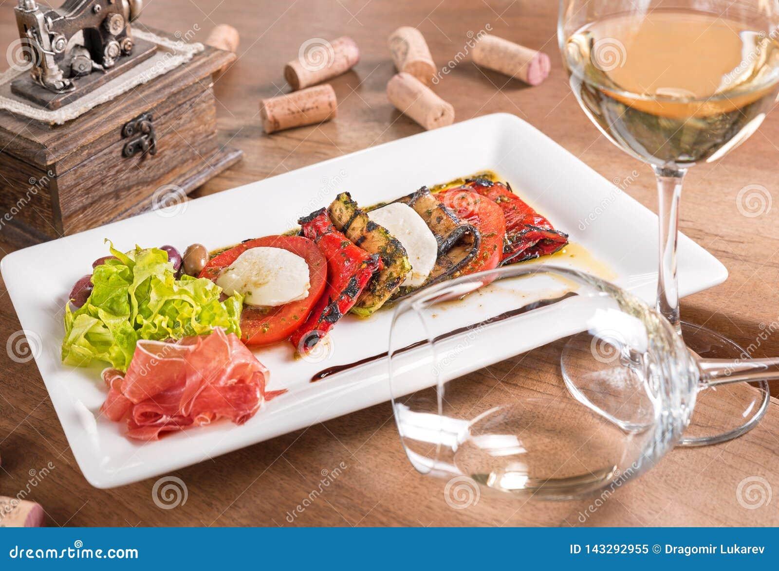 Antipasti z białym winem słuzyć w białym talerzu