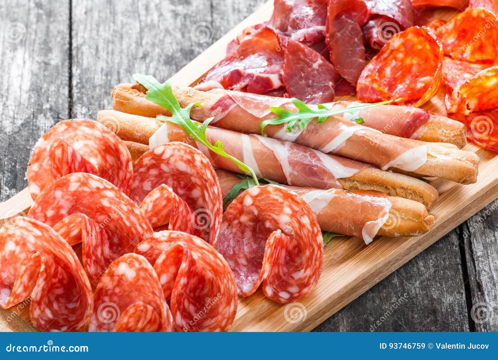 Antipasto półmiska zimnego mięsa talerz z grissini chlebowymi kijami, prosciutto, pokrajać baleron, wołowiny jerky, salami na tną