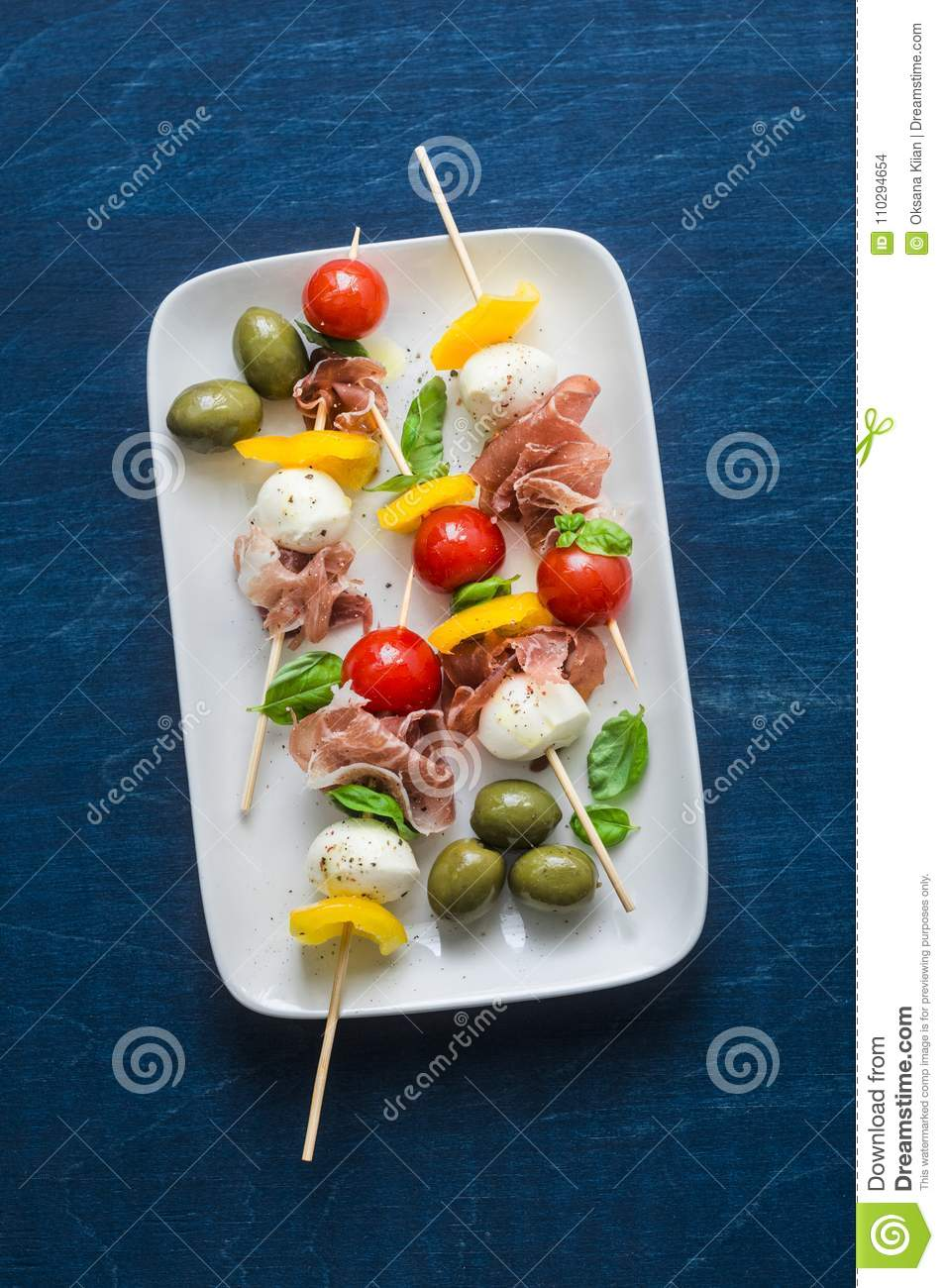 Antipasto skewers. Mediterranean appetizer to wine - prosciutto, bell peppers, cherry tomatoes, mozzarella cheese on skewers. Deli