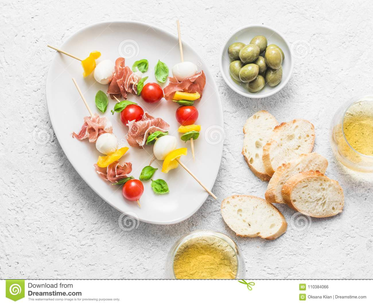 Antipasto skewers. Mediterranean appetizer to wine - prosciutto, bell peppers, cherry tomatoes, mozzarella cheese on skewers and w