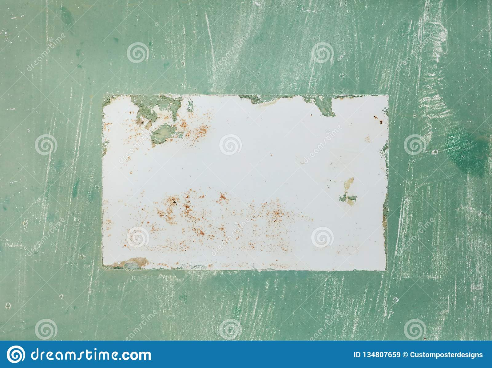 An antique aged sign with green textured paint and a white rectangle blank area in the middle.